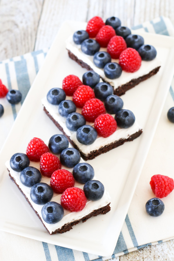 Gluten Free Vegan Berries and Cream Brownies. Fudgy brownies, topped with dairy free Cocowhip and rows of fresh berries. A deliciously patriotic dessert!