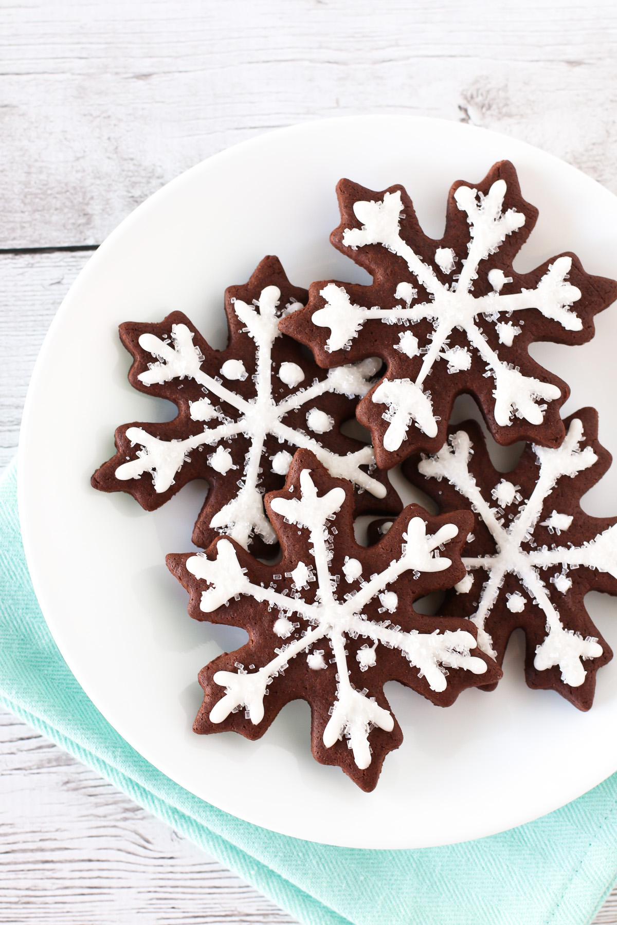 gluten free vegan chocolate snowflake sugar cookies decorated with a simple glaze and sparkling sugar