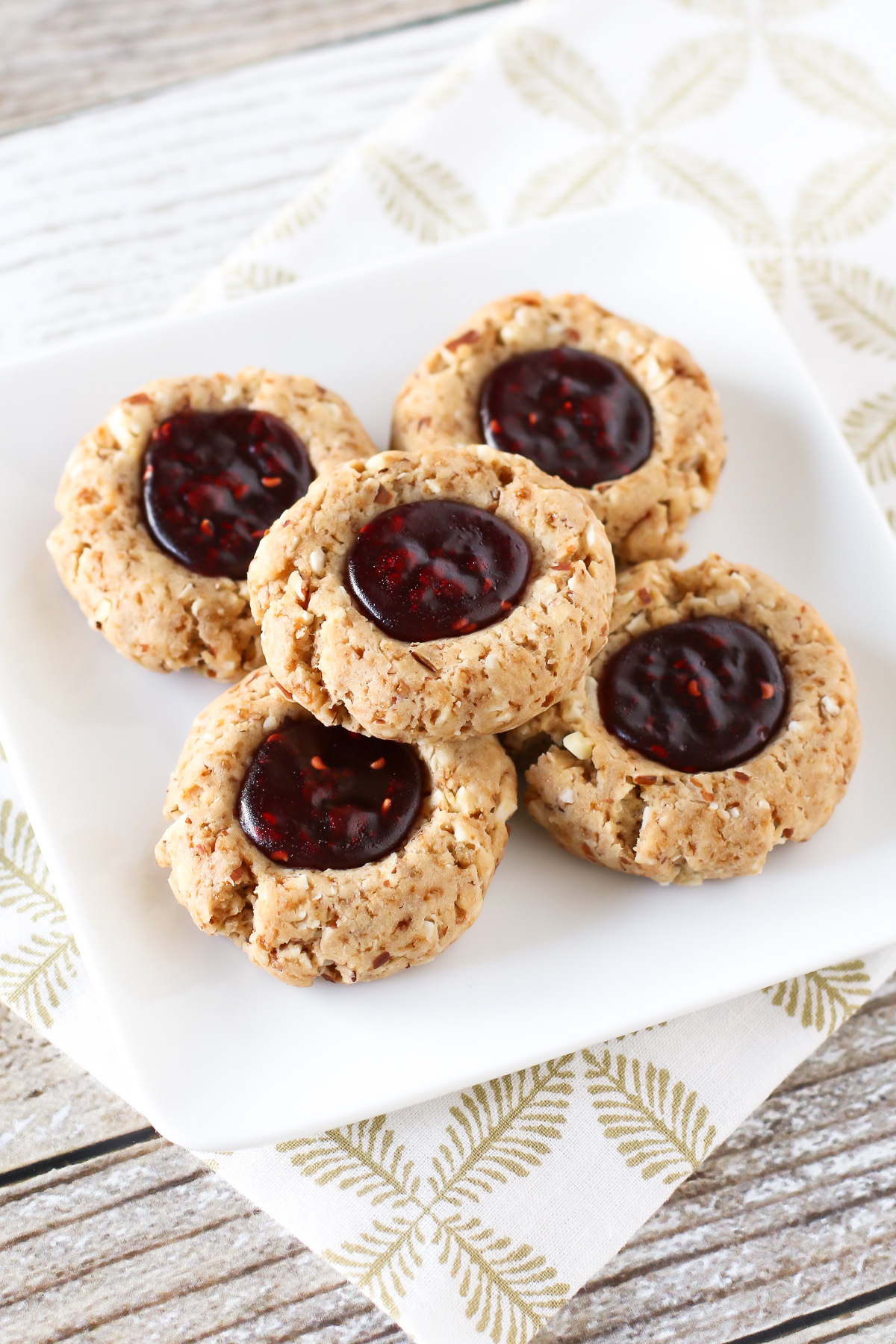 Gluten Free Vegan Raspberry Thumbprint Cookies. Tender almond cookies with a raspberry jam filling. A holiday classic!