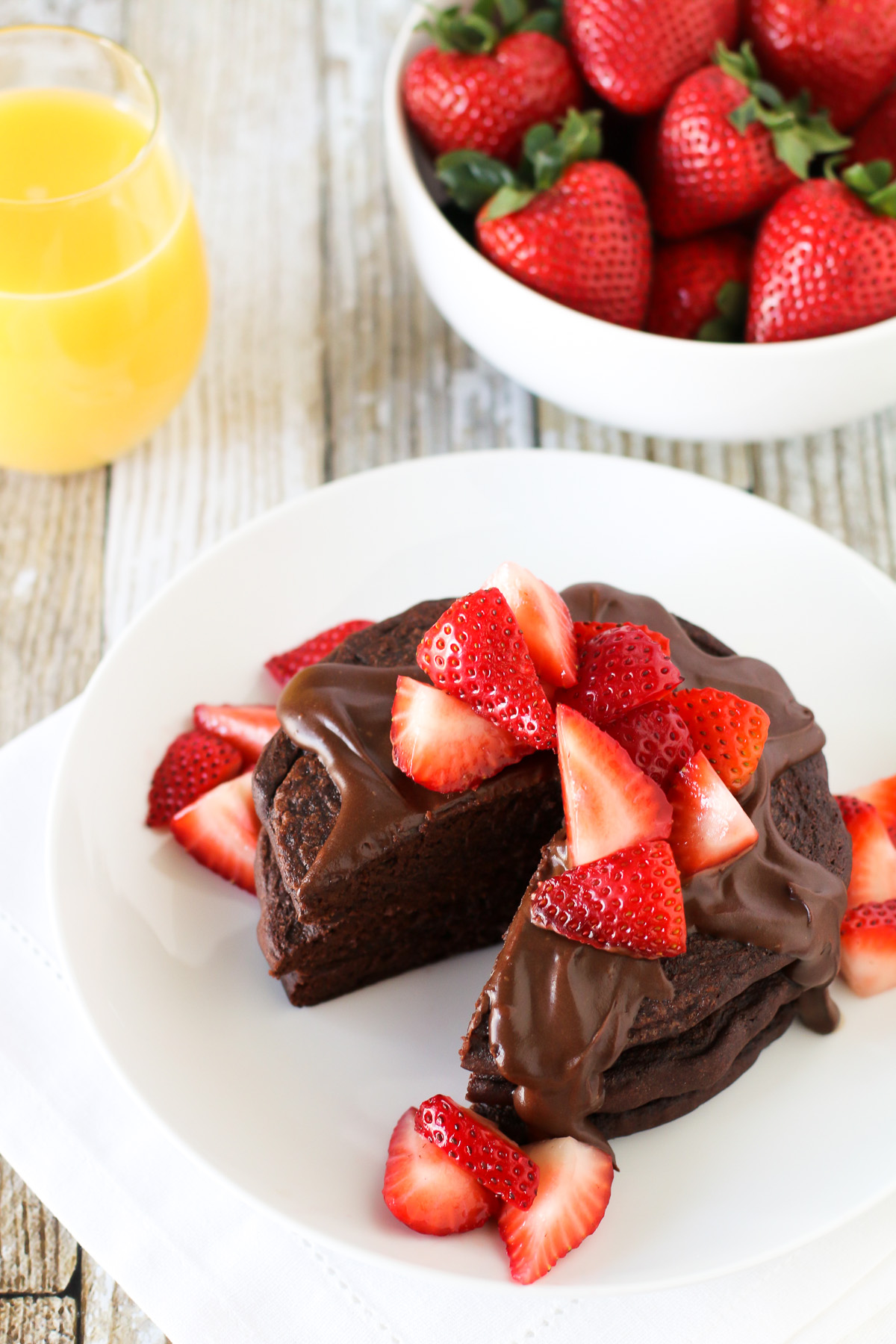 Gluten Free Vegan Double Chocolate Pancakes, featuring Bob's Red Mill egg replacer. Fluffy chocolate pancakes, covered in a simple chocolate sauce and fresh strawberries.