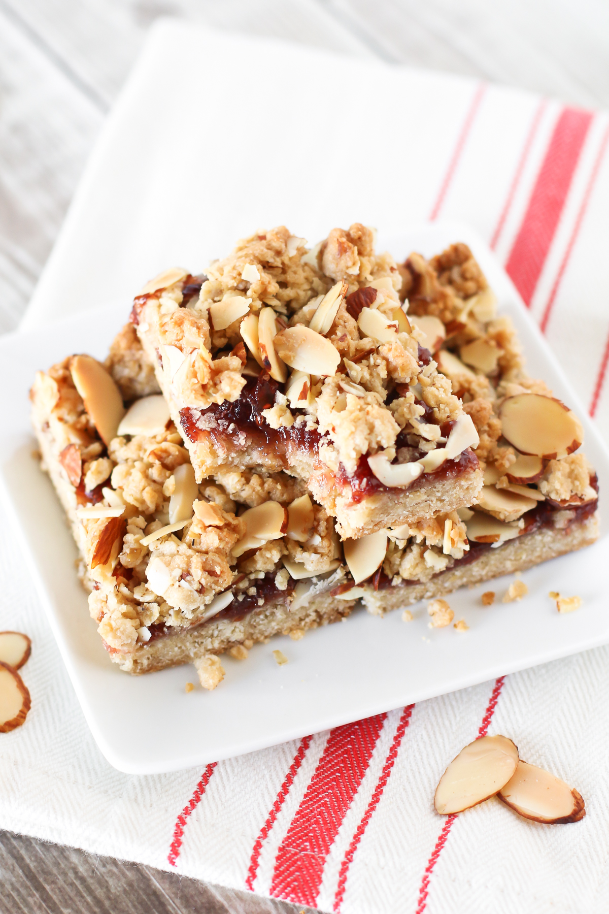 Gluten Free Vegan Raspberry Almond Crumb Bars. Layers of crumb topping, sweet raspberry jam and toasted almonds. The perfect bite!
