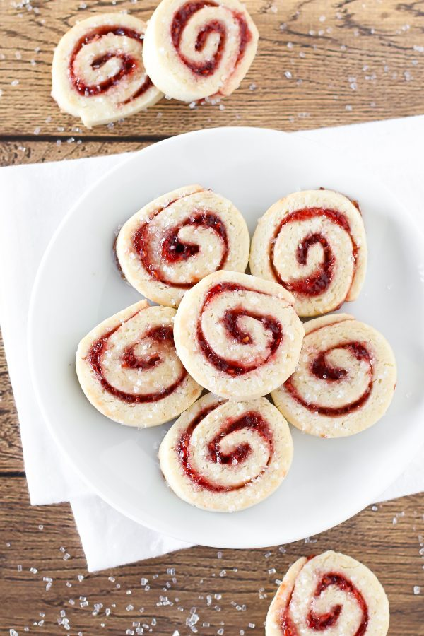 Gluten free vegan raspberry pinwheel cookies. What's not to love about a sugar cookie with a swirl of sweet raspberry jam and a sprinkling of sparkling sugar?