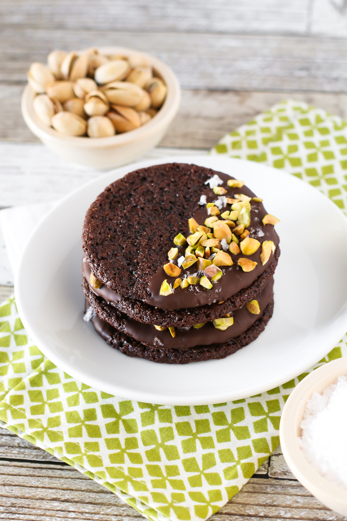 Grain Free Vegan Sea Salt Pistachio Chocolate Cookies. Chewy chocolate almond cookies, dipped in chocolate and sprinkled with chopped pistachios and sea salt.