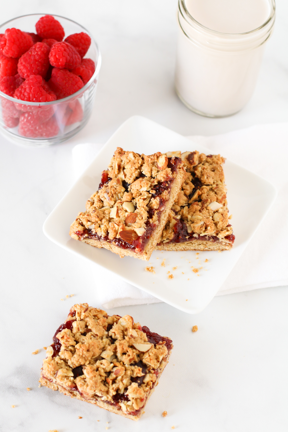 Gluten Free Vegan Raspberry Almond Breakfast Bars. These almond oat bars are slightly sweetened and filled with raspberry jam. A lovely on-the-go breakfast treat.