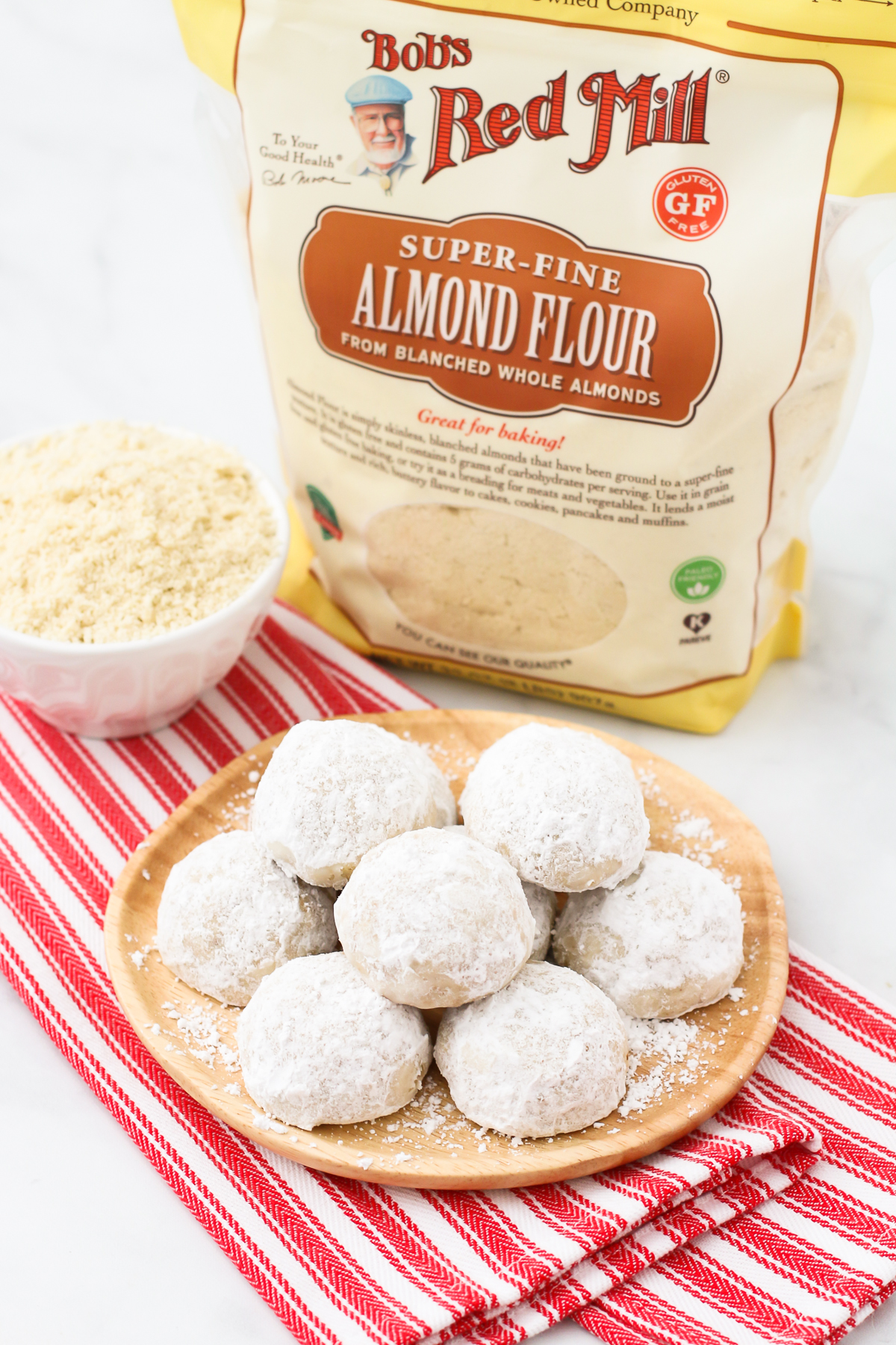 Gluten Free Vegan Snowball Cookies. These buttery, simple cookies are made with Bob's Red Mill almond flour and toasted walnuts. Festive and flavorful!