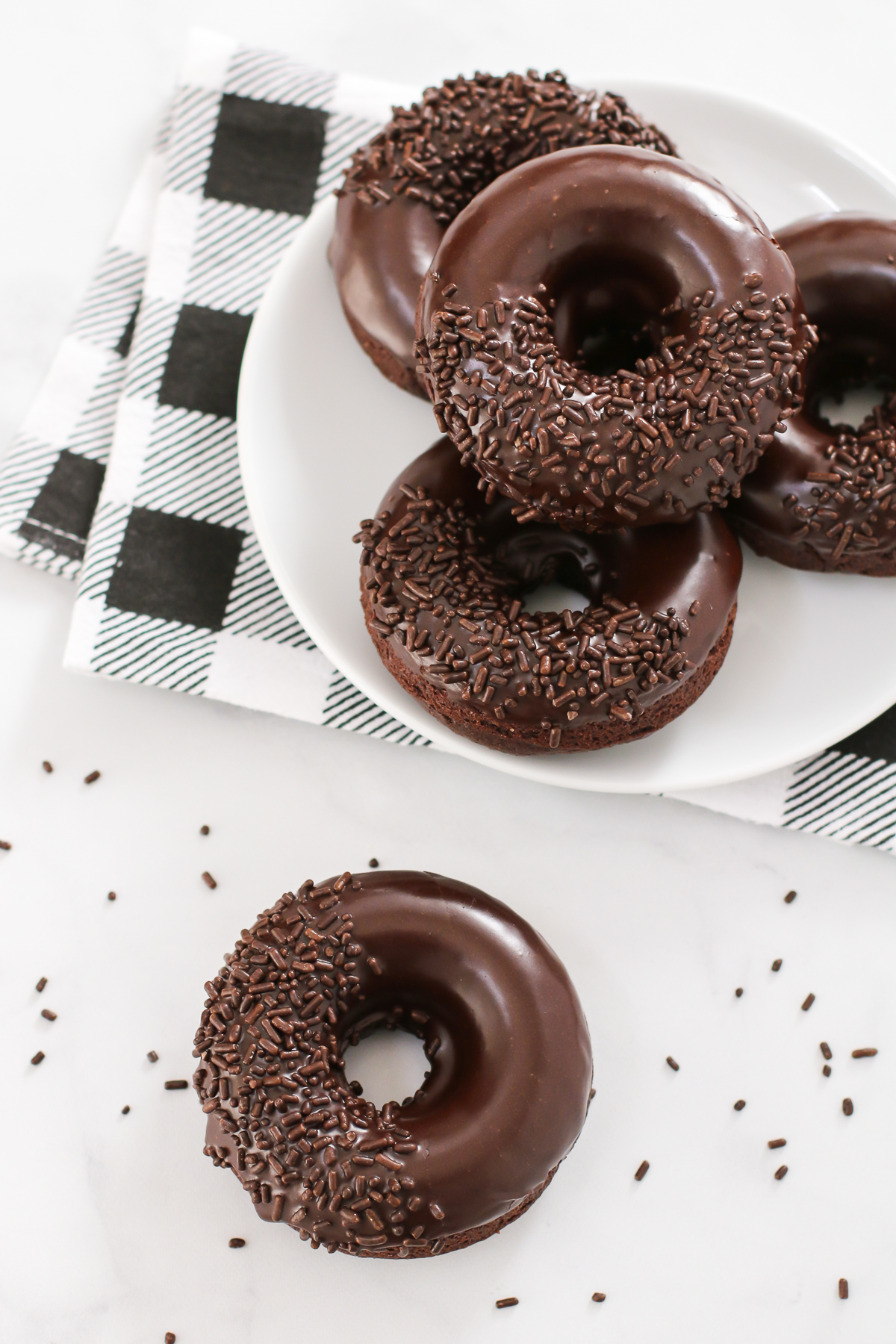 Gluten Free Vegan Baked Chocolate Donuts. Extra chocolatey cake donuts, dipped in a decadent chocolate glaze. Can't forget the chocolate sprinkles!