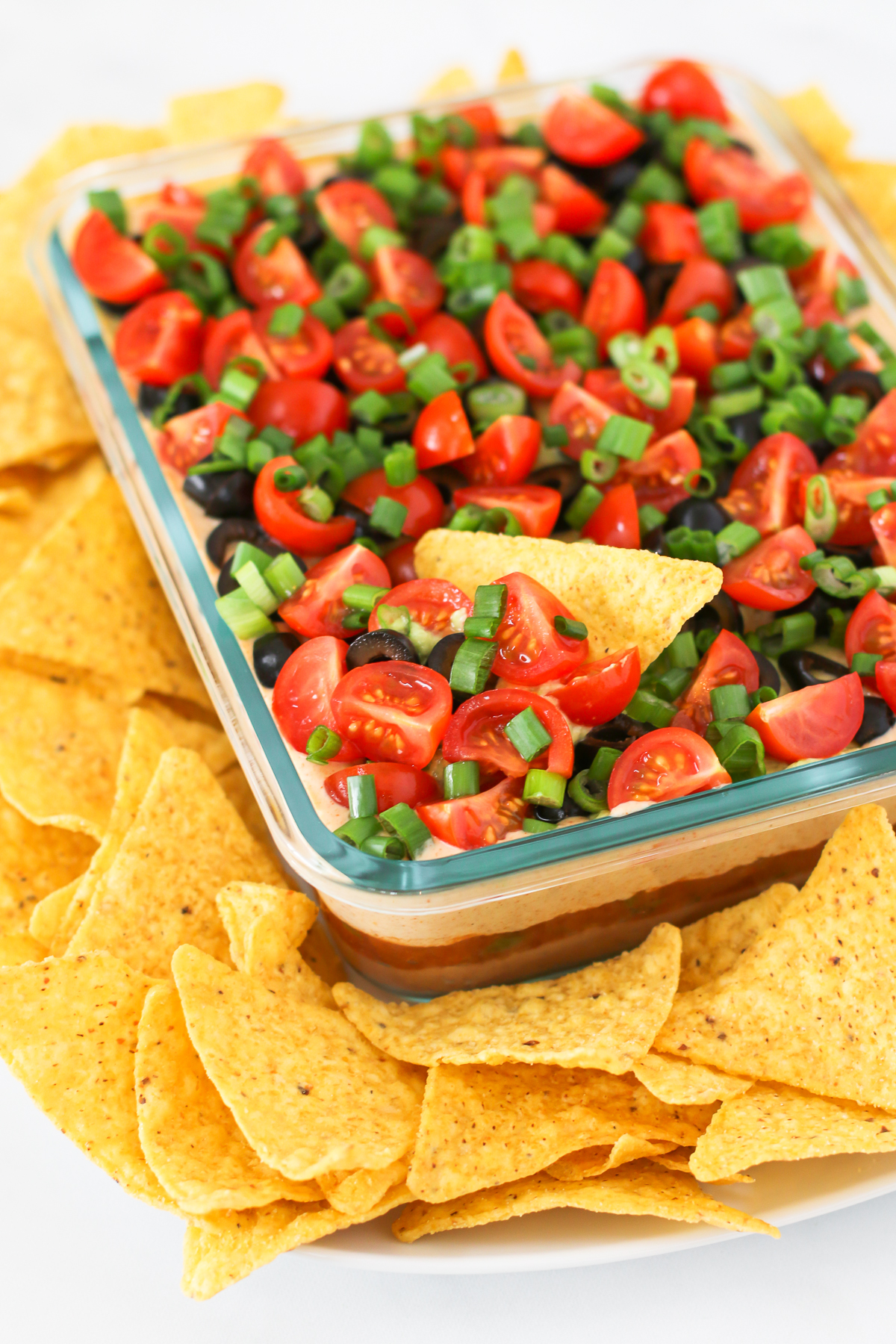 Vegan 7 Layer Bean Dip. Layers of beans, guacamole, creamy taco sauce, salsa and all of the vibrant Mexican flavors.