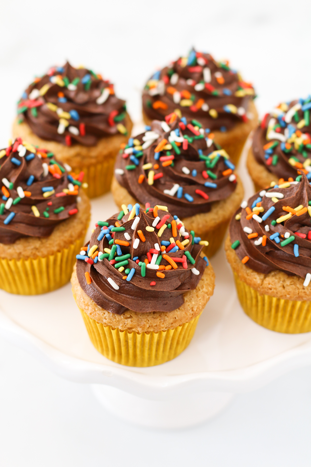 Gluten Free Vegan Vanilla Cupcakes with Chocolate Frosting. The classic flavors of a perfect vanilla cupcake, topped with a rich and creamy chocolate frosting.