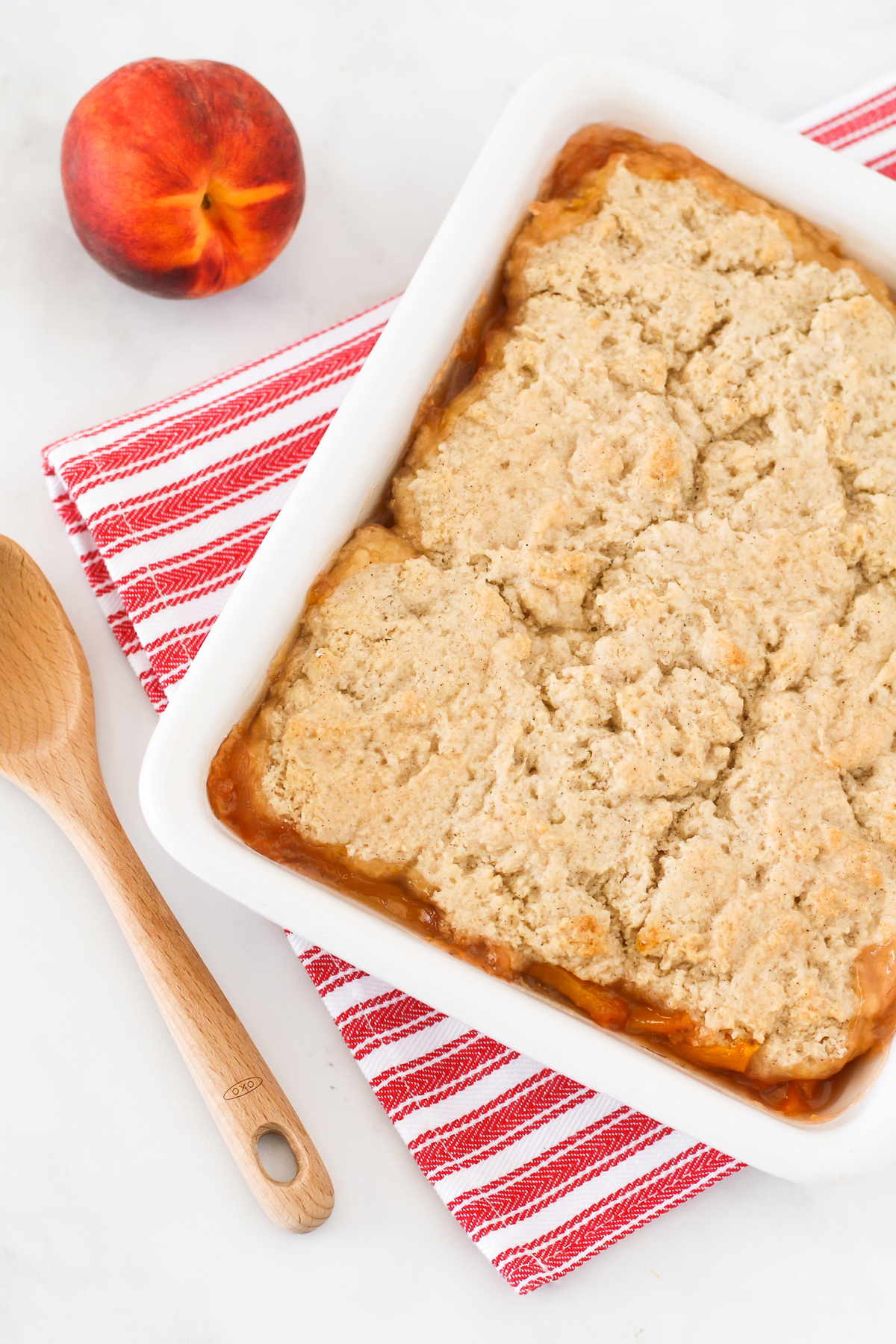 Gluten Free Vegan Peach Cobbler. Perfectly golden biscuit-like topping over sweet, juicy fresh peaches. The BEST summertime dessert!