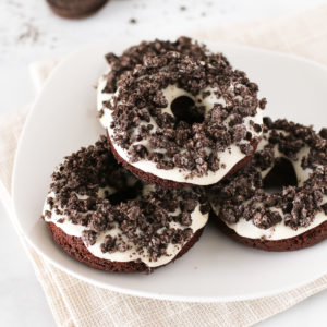 Gluten Free Vegan Cookies N' Cream Donuts. Baked chocolate donuts with a vanilla glaze, covered with crushed Oreo cookies. Oh so tasty!